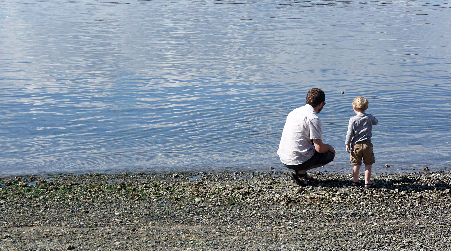Man and small boy skipping stones at the river.